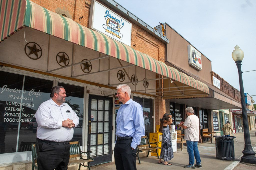 Jason Crawford (left) and Barry Moore visit with one another outside Javier's Cafe in the historic downtown square of Ferris on Thursday.