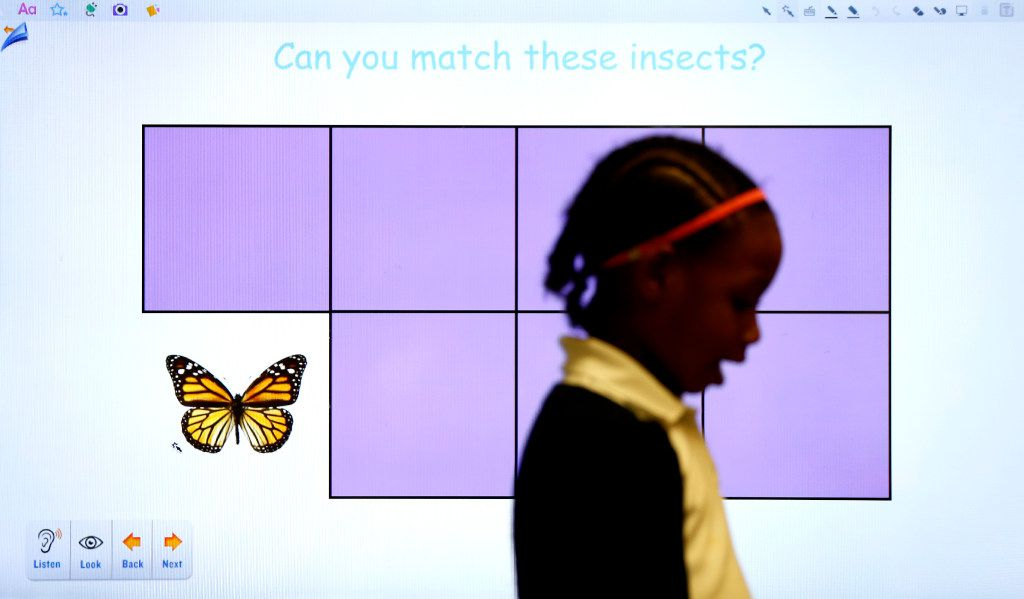 Mackenzie White plays in front of an interactive whiteboard in a pre-K classroom at N.W. Harllee Early Childhood Center in Dallas.