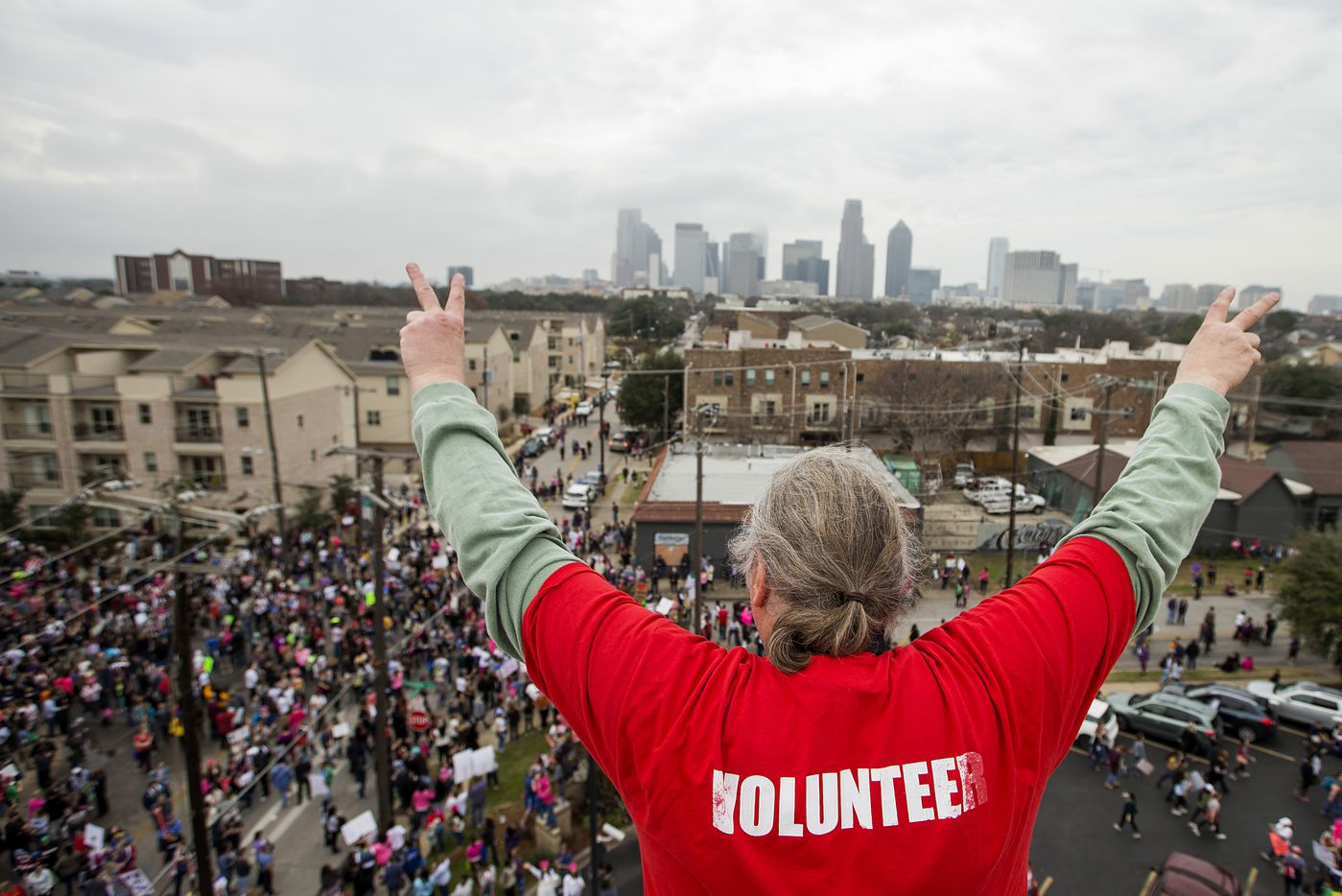 Herb Keener waves to participants reaching the end of the Dallas Women's March from atop the roof of the at the Communications Workers of America Hall on Washington on Saturday, Jan. 21, 2017, in Dallas.  The Dallas event was held in solidarity with the Women's March on Washington.
