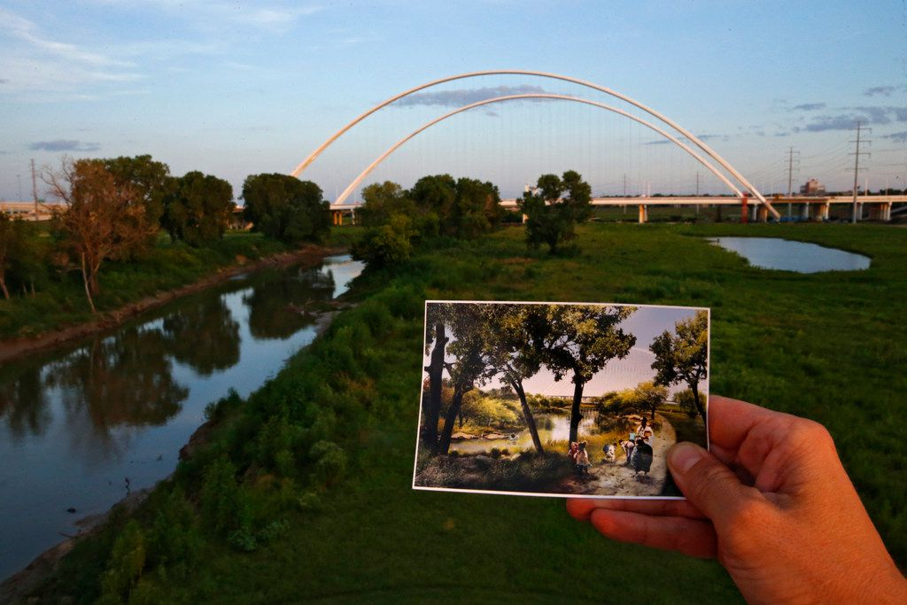 A photograph of the proposed Trinity River park area is held in front of the Interstate 30 Margaret McDermott Bridge in Dallas.