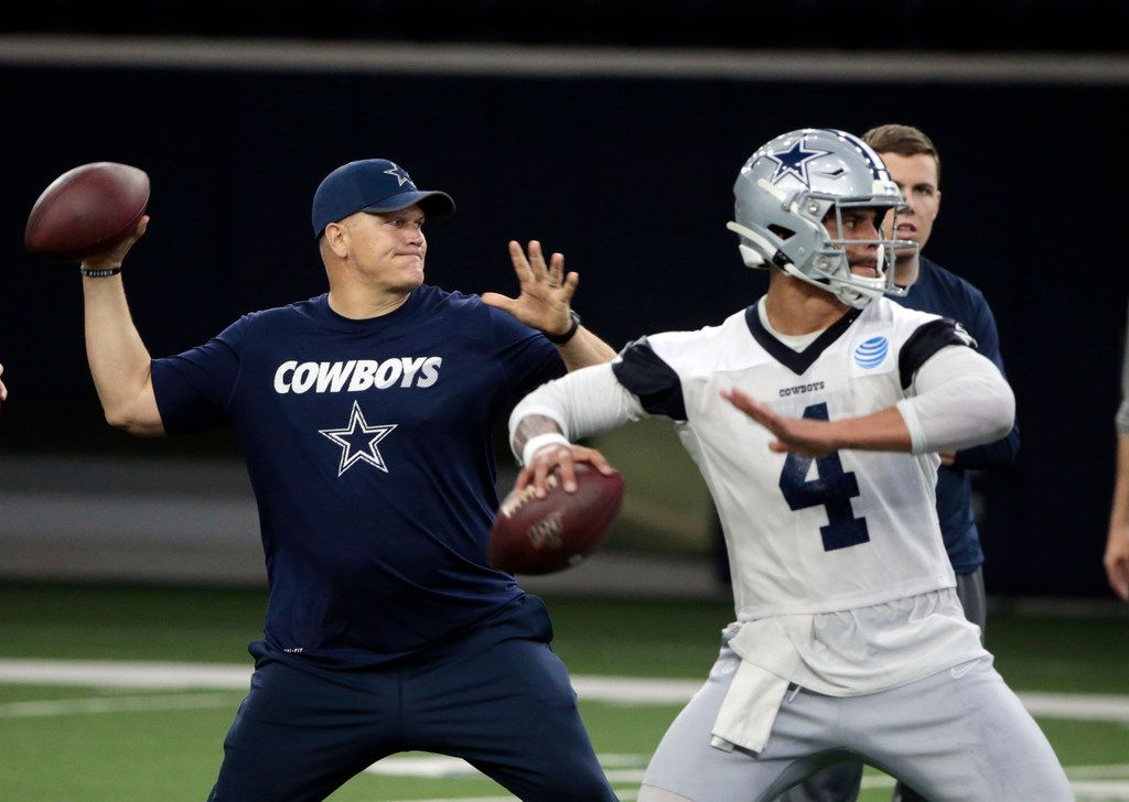 Dallas Cowboys quarterbacks coach Jon Kitna throws the ball alongside Dak Prescott (4) during NFL football practice in Frisco, Texas, Wednesday, May. 22, 2019. (AP Photo/Michael Ainsworth)