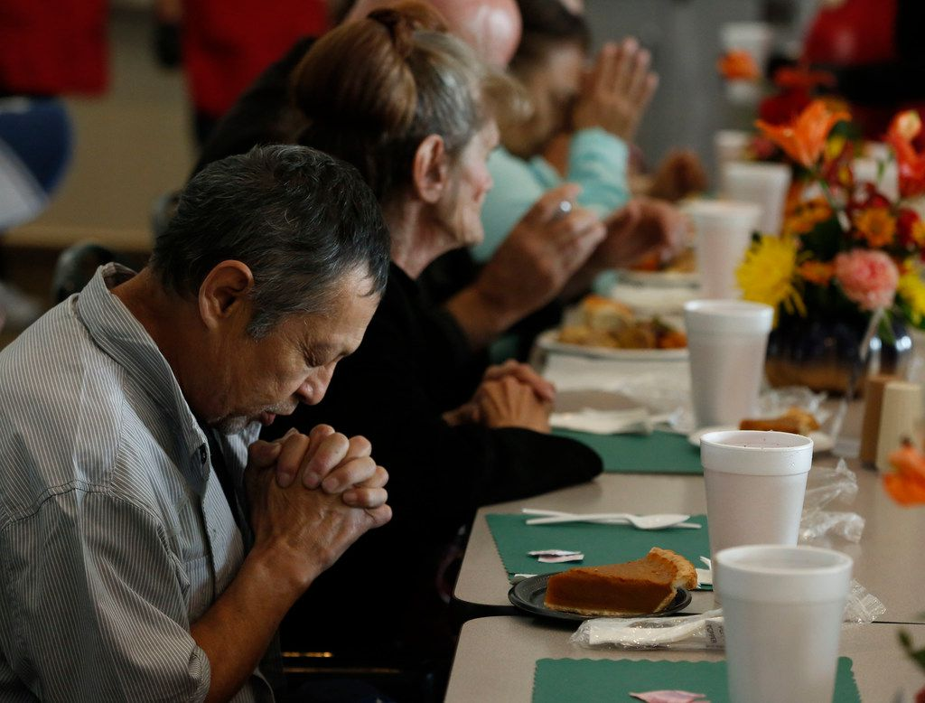 Robert Camacho prays before eating his Thanksgiving meal at The Salvation Army in Dallas on Nov. 22, 2018. The Salvation Army serves than 1,500 traditional Thanksgiving Day meals with all the trimmings  to homeless individuals and families who cannot afford them. (Nathan Hunsinger/The Dallas Morning News)
