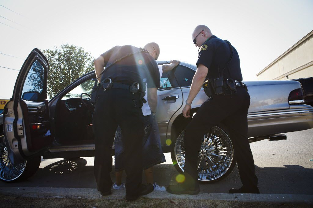 Dallas Police Officers Bryan Burgess and Lance Wreyford arrest a man for outstanding warrants at Lake June and  Buckner in the Pleasant Grove area on Tuesday, September 27, 2011 in Dallas. (Patrick T. Fallon/The Dallas Morning News) 12132011xMETRO