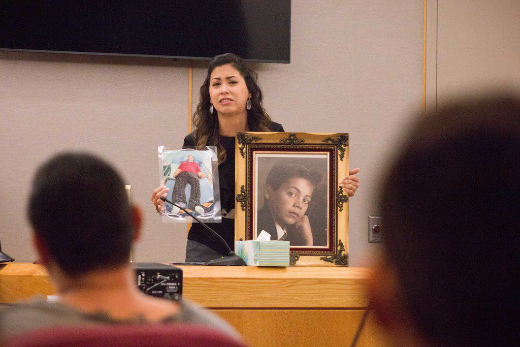 "Veronica Garcia, whose brother Jose ""Pepe"" Villegas was paralyzed in a shooting that killed her uncle in May 1992, holds photos of her brother as she speaks to Joseph Buckaloo. Buckaloo pleaded guilty to the murder Tuesday and was sentenced to 30 years in prison."
