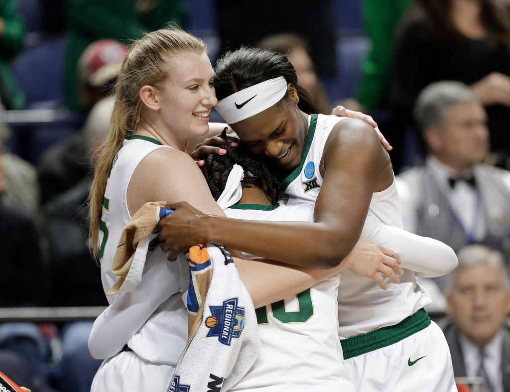 Baylor's Lauren Cox, left, Kalani Brown, right, and Juicy Landrum, center, hug as they celebrate their win over Iowa in the closing moments of the second half of a regional final women's college basketball game in the NCAA Tournament in Greensboro, N.C., Monday, April 1, 2019. (AP Photo/Chuck Burton)