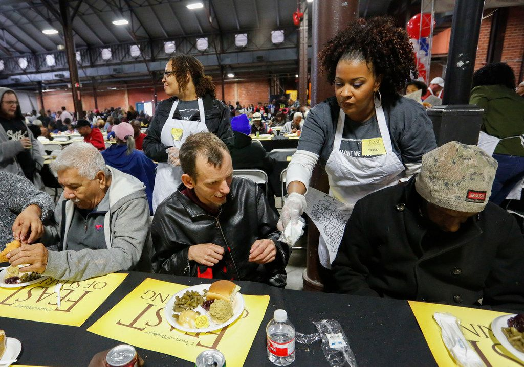 Jonathan Hale (center) was served a full Thanksgiving meal from volunteer Valerie Walter at Central Market's Feast of Sharing at Fair Park's Centennial Building on Nov. 9. (Ron Baselice/Staff Photographer)