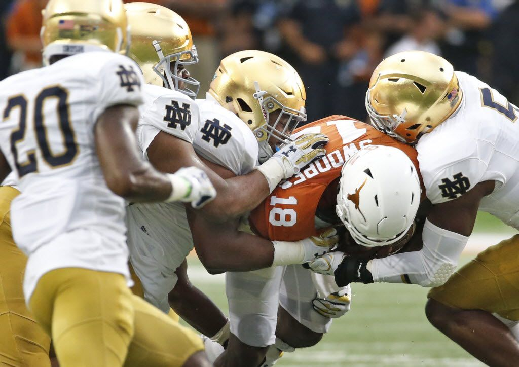 A host of Notre Dame defenders brings down Texas quarterback Tyrone Swoopes (18) in the second quarter during the Notre Dame Fighting Irish vs. the University of Texas Longhorns NCAA football game at Darrell K. Royal Memorial Stadium in Austin on Sunday, September 4, 2016. (Louis DeLuca/The Dallas Morning News)