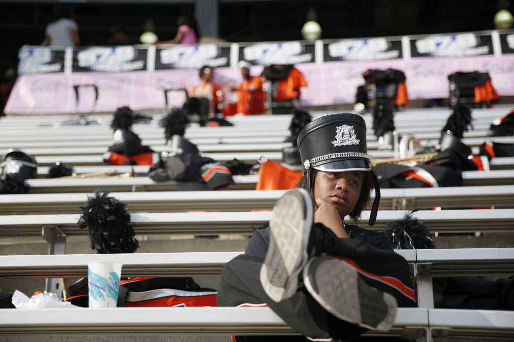 Clarinet player Jade Jeffrey, 15, of Lancaster, Texas, sits alone watching the game after the Lancaster High School marching band performed before a college football game between Grambling and Prairie View A&M in the State Fair Classic game at the Cotton Bowl in Dallas Saturday Sept. 27, 2014.