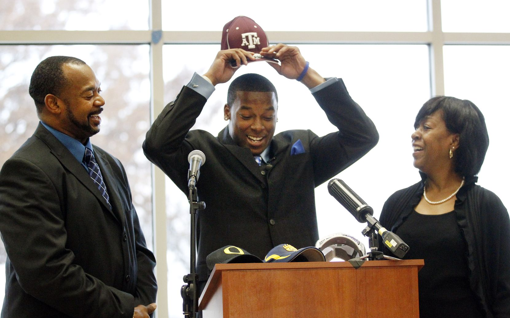 Skyline High wide receiver Thomas Johnson (center) puts on a Texas A&M cap, as father Robert and stepmother Sabrina watch, after committing to play football for the school, signing a National Letter of Intent at a ceremony held in the Skyline High School cafeteria on Wednesday, February 1, 2012. Johnson is the No. 2-ranked high school recruit in the area. (John F. Rhodes / Special Contributor)