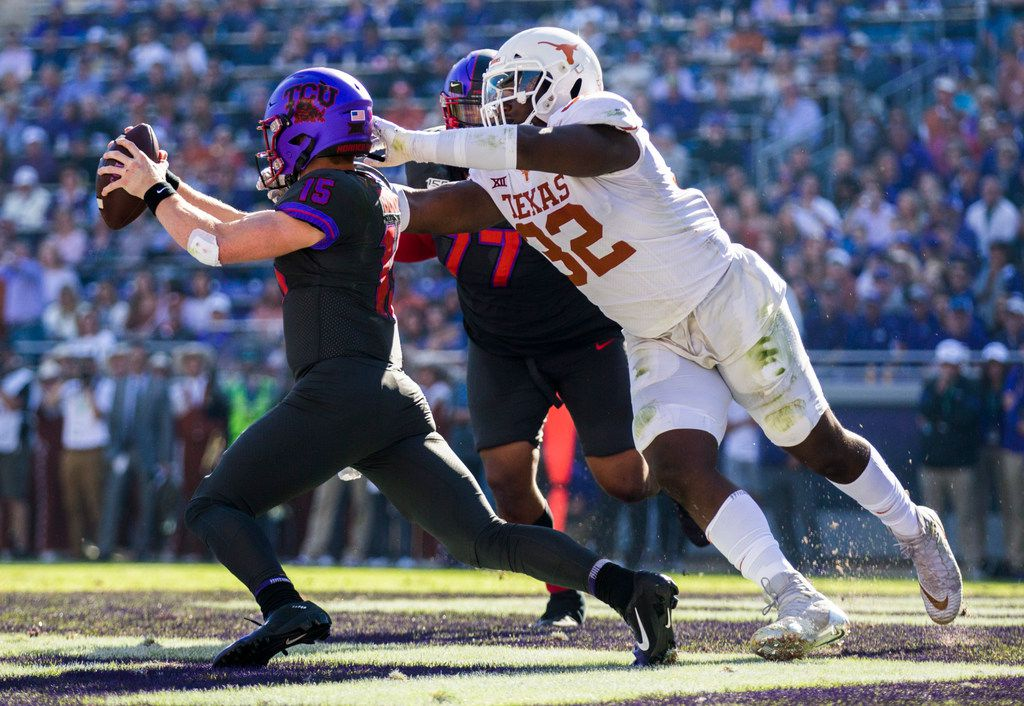 TCU Horned Frogs quarterback Max Duggan (15) avoids a safety attempt by Texas Longhorns defensive lineman Malcolm Roach (32) during the Horned Frogs' 37-27 win over Texas on Saturday, October 26, 2019 at Amon G Carter Stadium in Fort Worth. (Ashley Landis/The Dallas Morning News)
