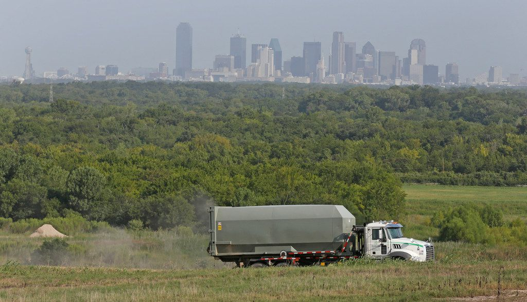 With the downtown Dallas skyline in the background, a truck moves through the McCommas Bluff Landfill at 5100 Youngblood Road in Dallas.