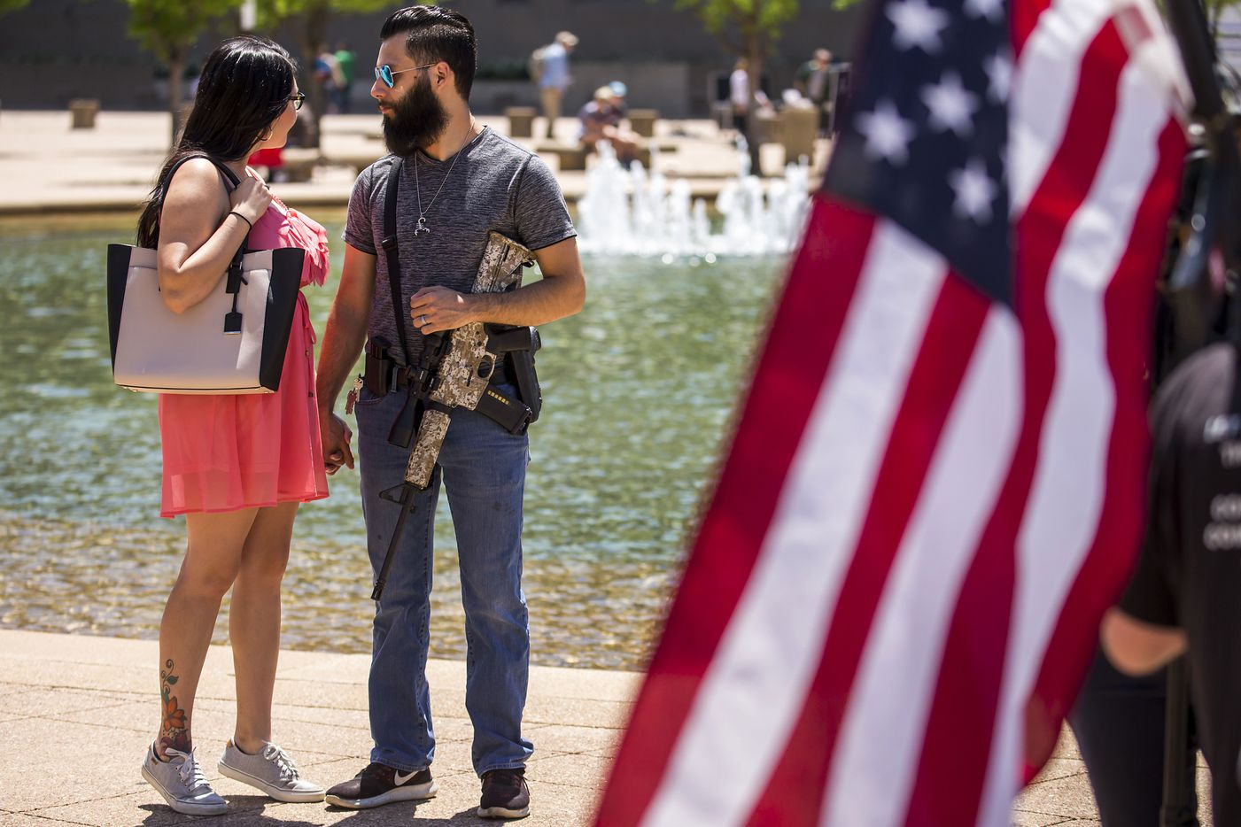Jessica Scogin holds hands with her husband Ryan Scogin as gun rights advocates demonstrate outside Dallas City Hall at a rally organized by Open Carry Texas during the NRA Annual Meeting & Exhibits at the Kay Bailey Hutchison Convention Center on Saturday, May 5, 2018, in Dallas.