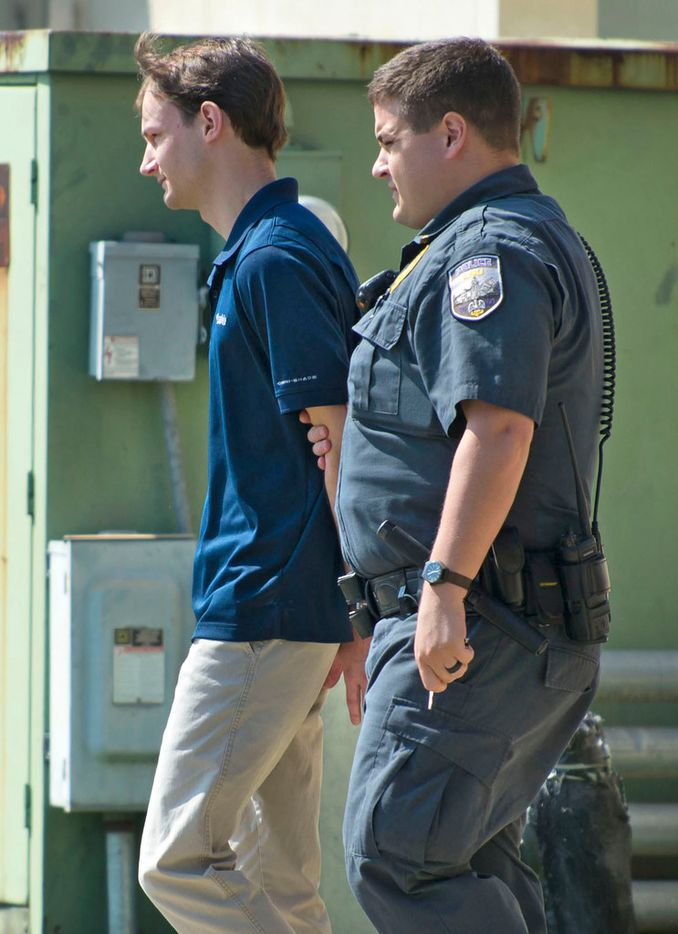 Matthew Alexander Naquin, is escorted from LSU Police Dept. headquarters by LSU Police Dept. officers after being booked on a hazing charge on Wednesday, Oct. 11, 2017 in Baton Rouge, La. Multiple people were arrested Wednesday on hazing charges in the death of Maxwell Gruver, a Louisiana State University fraternity pledge whose blood-alcohol content level was more than six times the legal limit for driving, officials said.  Naquin also faces a negligent homicide charge.   (Travis Spradling/The Advocate via AP)
