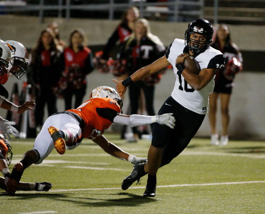 Euless Trinity's Valentino Foni (16( gets away from a tackle by Haltom's Gavon Lange (24) to score a touchdown during the second half of their high school football game on Oct. 11, 2019 in North Richland Hills. Haltom defeated Trinity 23-20. (Michael Ainsworth/Special Contributor)