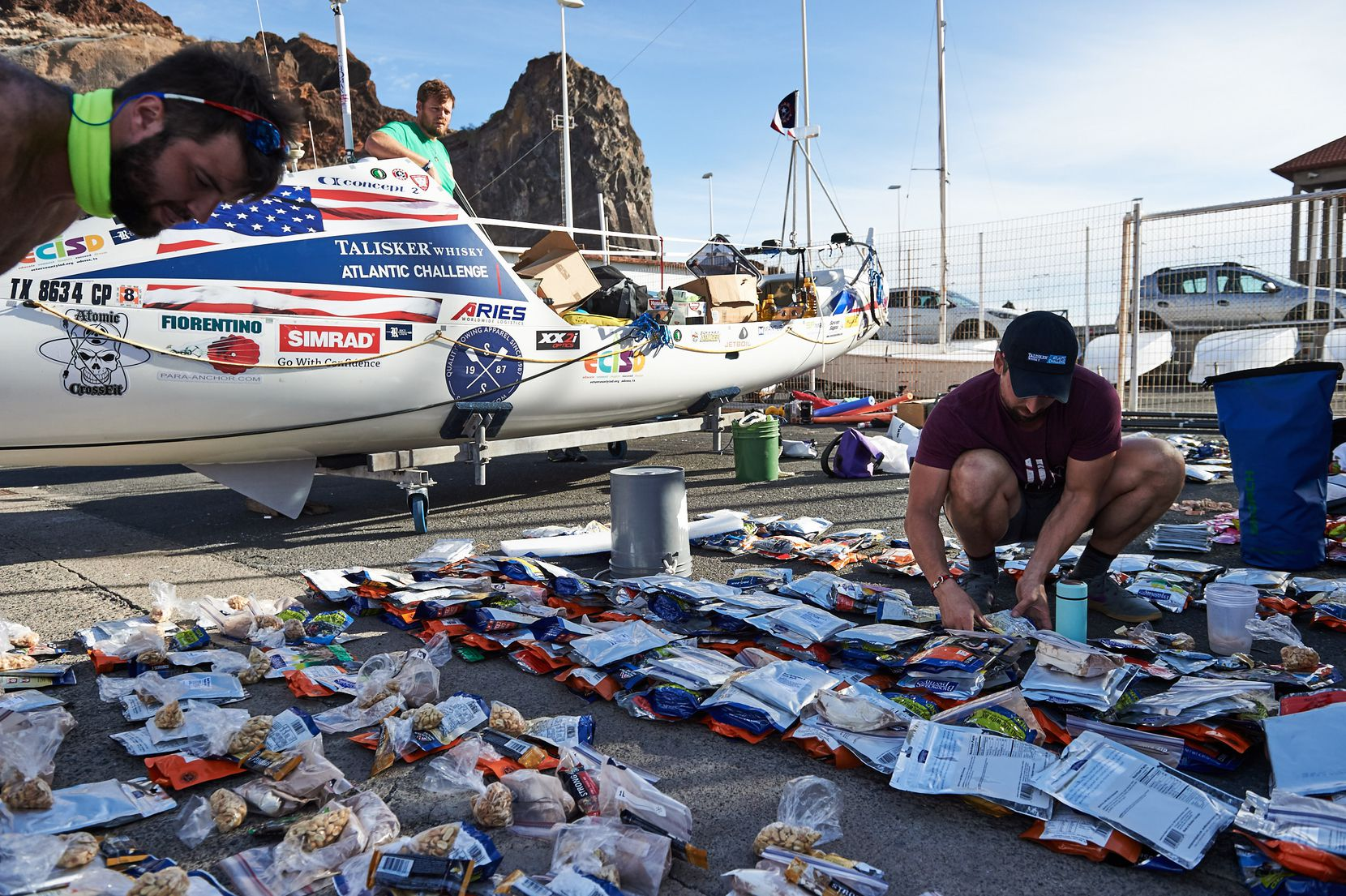 The American Oarsmen prepare their stock of meal rations before the start of the trip. From left are Krauskopf (top left corner), Matson (on the boat) and Alviar.