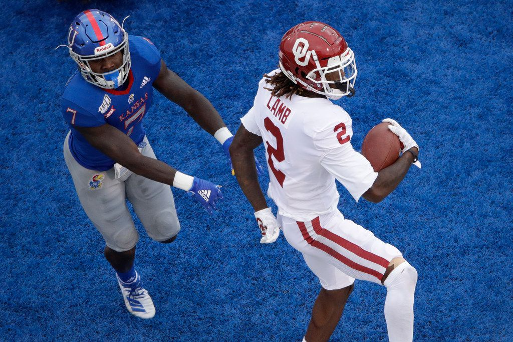 Oklahoma wide receiver CeeDee Lamb (2) beats Kansas safety Davon Ferguson (7) into the end zone to score a touchdown during the first half of an NCAA college football game Saturday, Oct. 5, 2019, in Lawrence, Kan. (AP Photo/Charlie Riedel)