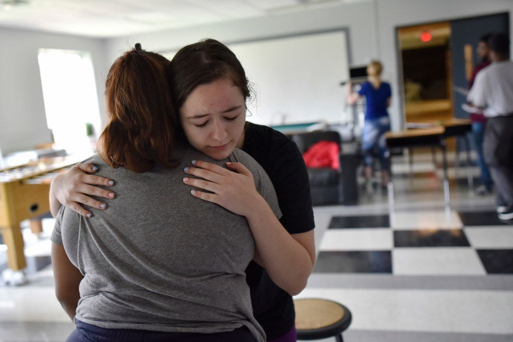 Emma Burkey, 16, (right) hugs Cicsy Rojas, 17, during a rehearsal of Sex Ed.