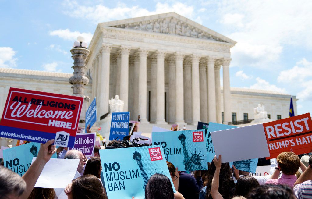 Protesters hold up signs and call out against the Supreme Court ruling upholding President Donald Trump's travel ban outside the the Supreme Court in Washington, Tuesday, June 26, 2018.