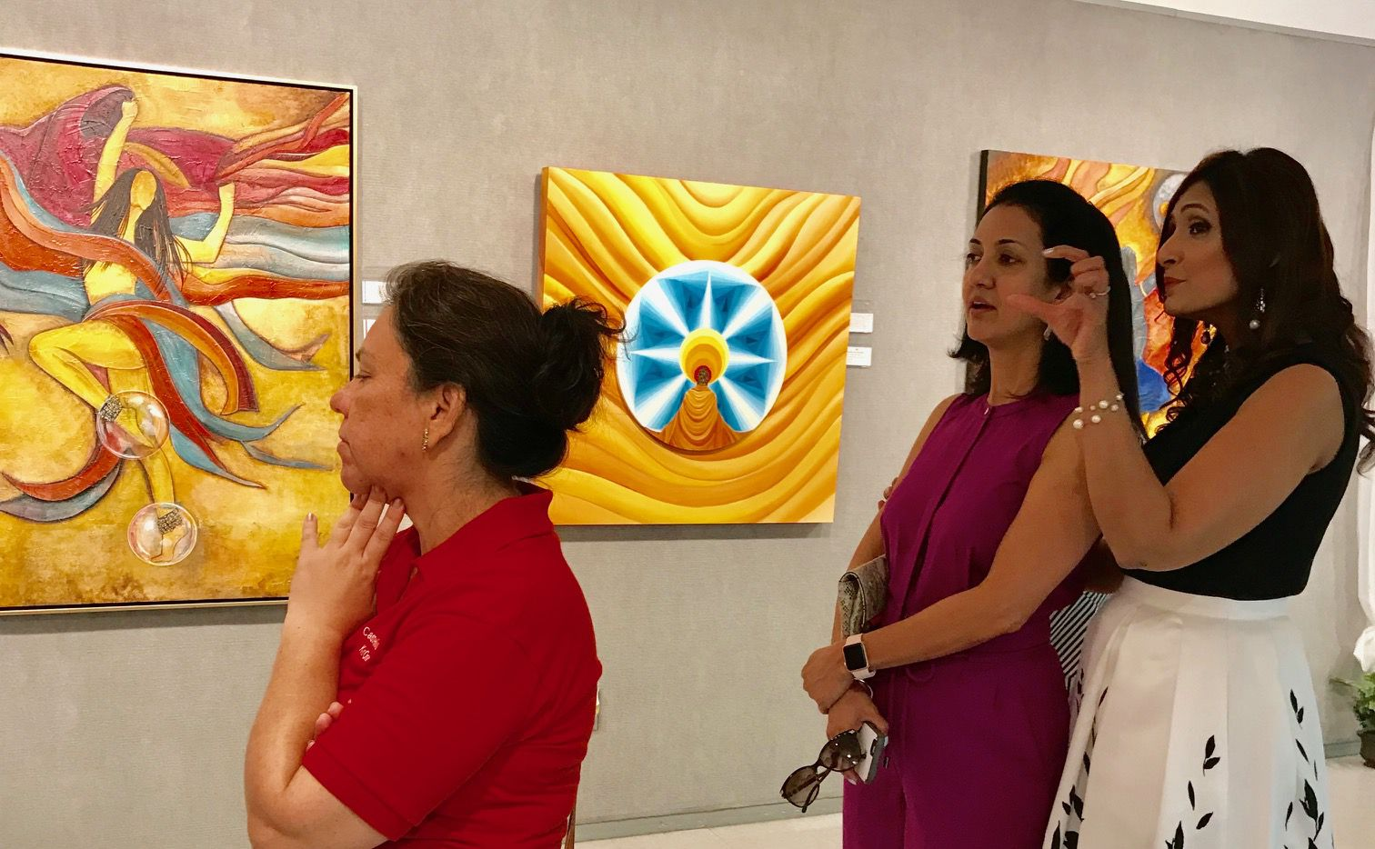 "Artist Navneeta Khemka talks about her paintings with guests at a reception for her exhibit called ""Sound of Music,"" which runs through May 25 at Jaycee Park Center for the Arts, 1975 Puritan Drive in Irving."