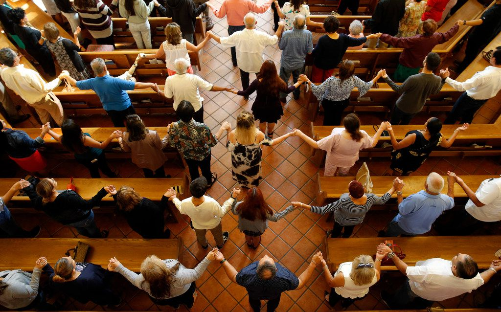 Congregation held hands as they sang during a morning service at St. Pius X Church in El Paso on Sunday, August 4, 2019.