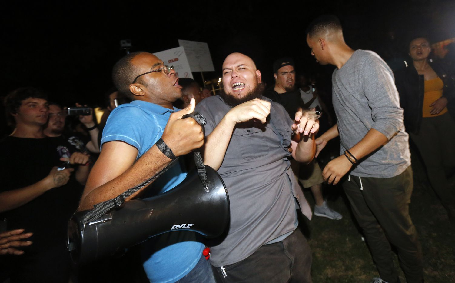Aaron Cartwright of Dallas (left) and Andre Nihilist of Fort Worth clash during a protest at Pioneer Park, across the street form the March Against White Supremacy rally.