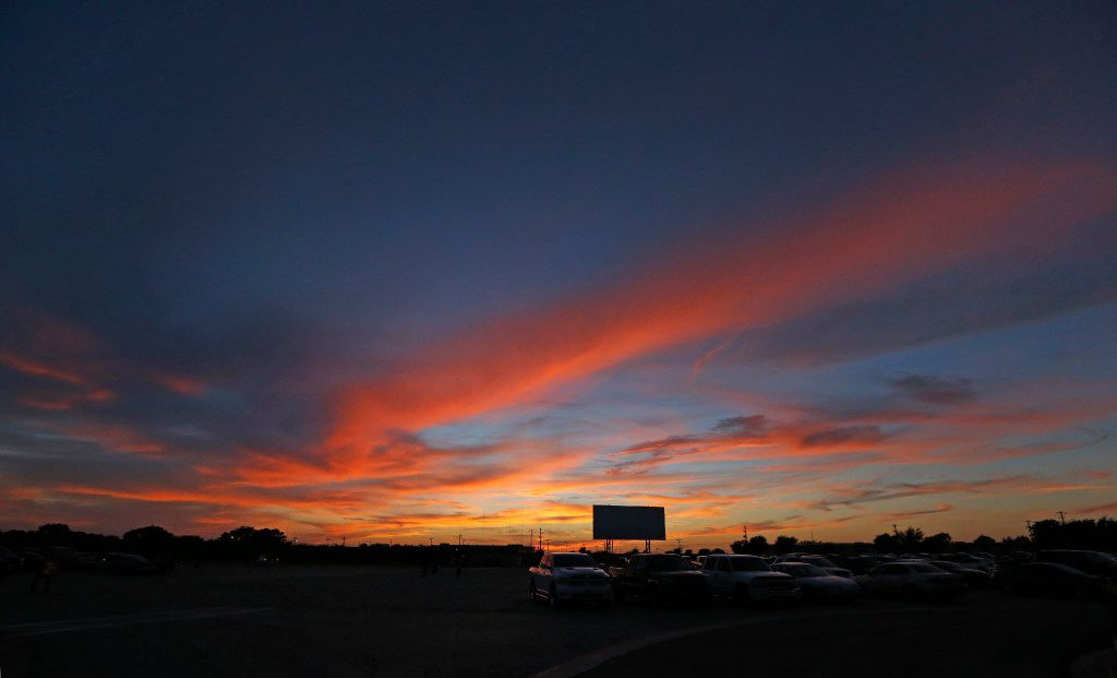 The sun sets behind one of the screens at the Coyote Drive-In in Lewisville, Texas, photographed on Saturday, October 29, 2016. (Louis DeLuca/The Dallas Morning News)
