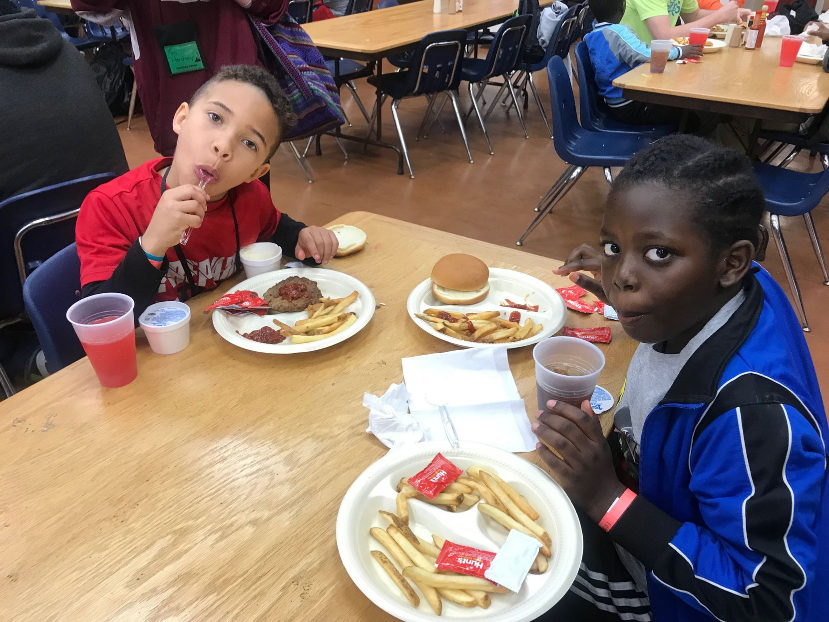 Chris Rokundo, 9, (left) and Daetin Sanders, 8,  eat lunch at Cowboy Camp.