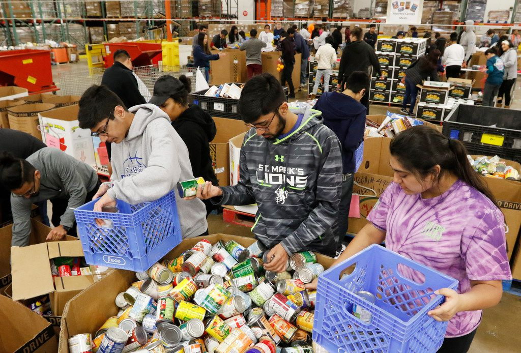 Ozair Kamran (from left), his brother, Daniyaal Kamran, and sister, Danees Kamran, sorted food at the North Texas Food Bank on South Cockrell Hill Road in Dallas in December 2017.