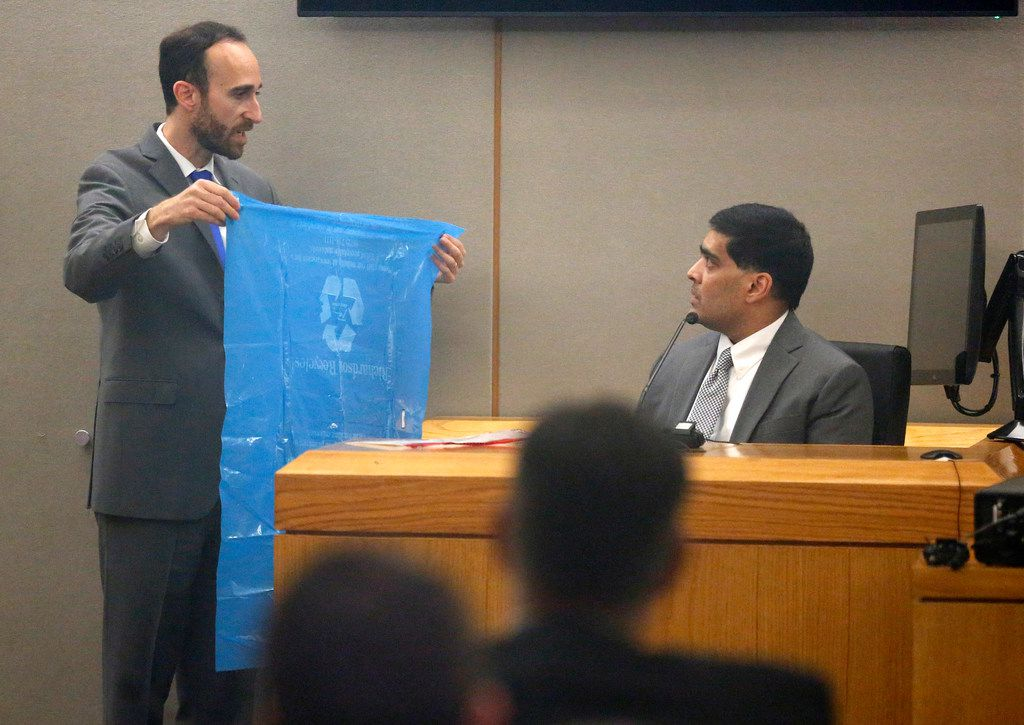 Prosecutor Jason Fine cross-examines Wesley Mathews in court Wednesday, showing him a blue plastic bag that 3-year-old Sherin Mathews' body was found wrapped in.