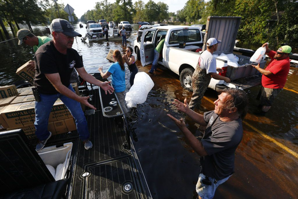 Volunteers Brooks Bonin (left) and Eugene Collins load boats on Sept. 3 in Vidor to resupply the community of Pine Forest, which is among those hit hard by flooding from Harvey.