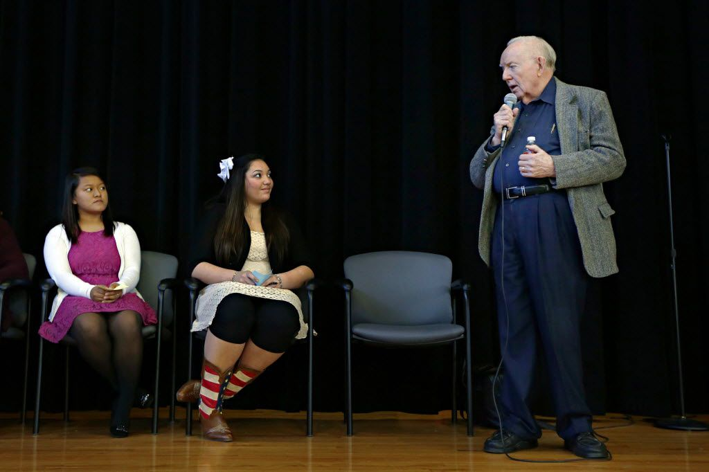 Dr. Robert McClelland spoke as students Sylvia Mualcin (left) and Kayla Conner listened on stage during a presentation at Lewisville High School-Harmon Campus in November 2013.