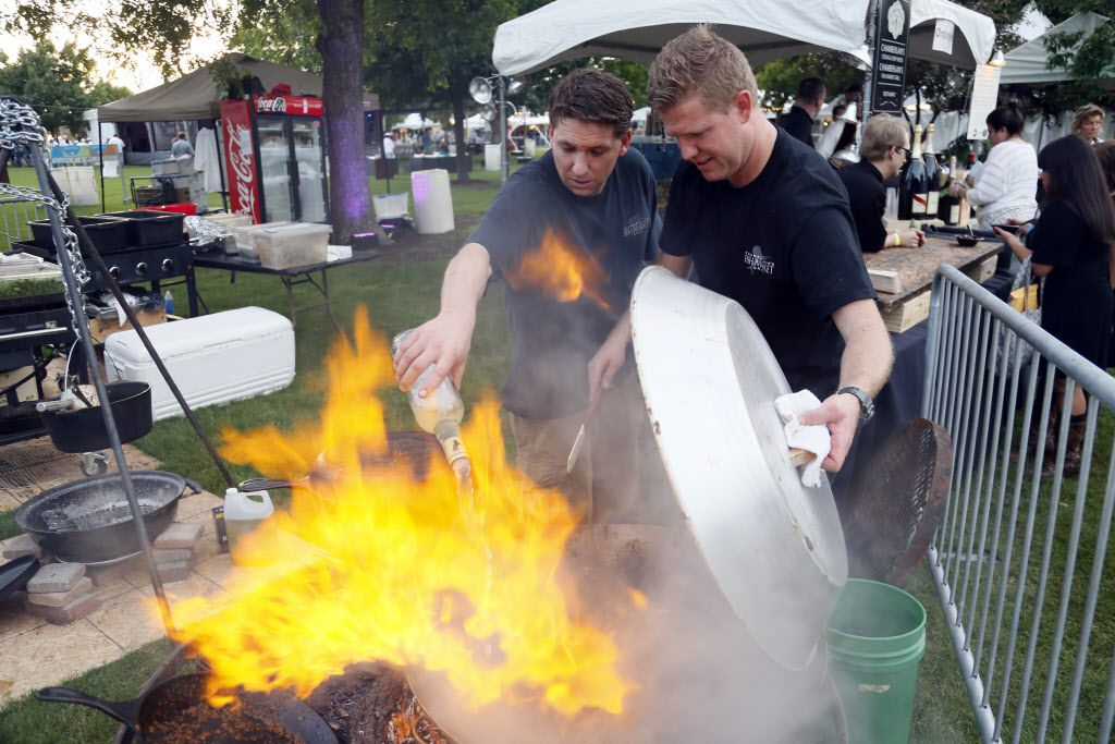 Hugh Stewart, left, and Jared Coffey, right, chefs from Chamberlain's Fish Market Grill cook mussels together during the Fork & Cork festival Addison Circle Park in Addison, TX on May 15, 2015.