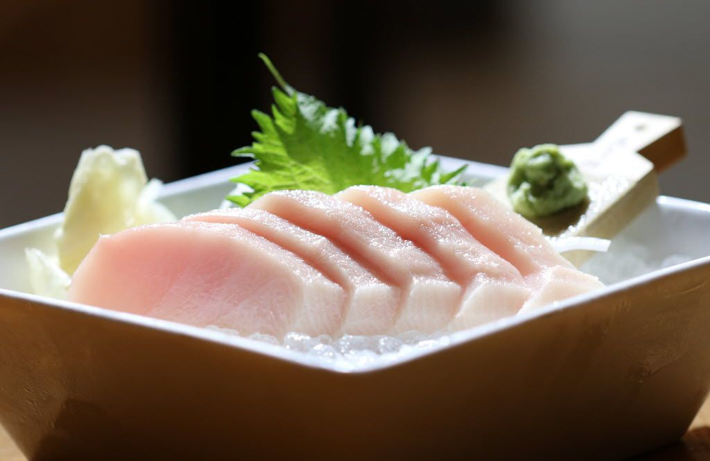 Hamachi sashimi garnished with wasabi (on the wooden paddle at right) and shiso (the leaf in the background) at Sushi Bayashi