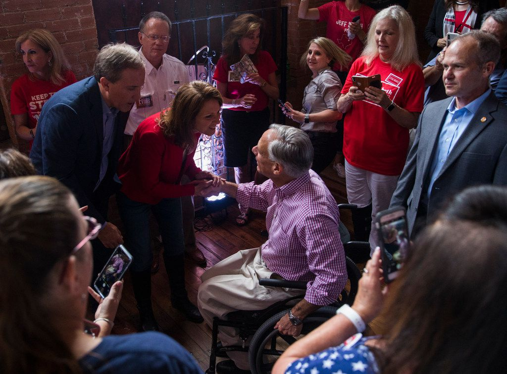 Texas Gov. Greg Abbott greets Attorney General Ken Paxton and his wife Angela Paxton before speaking at a Collin County Republican Party event Monday, September, 3, 2018, in McKinney.