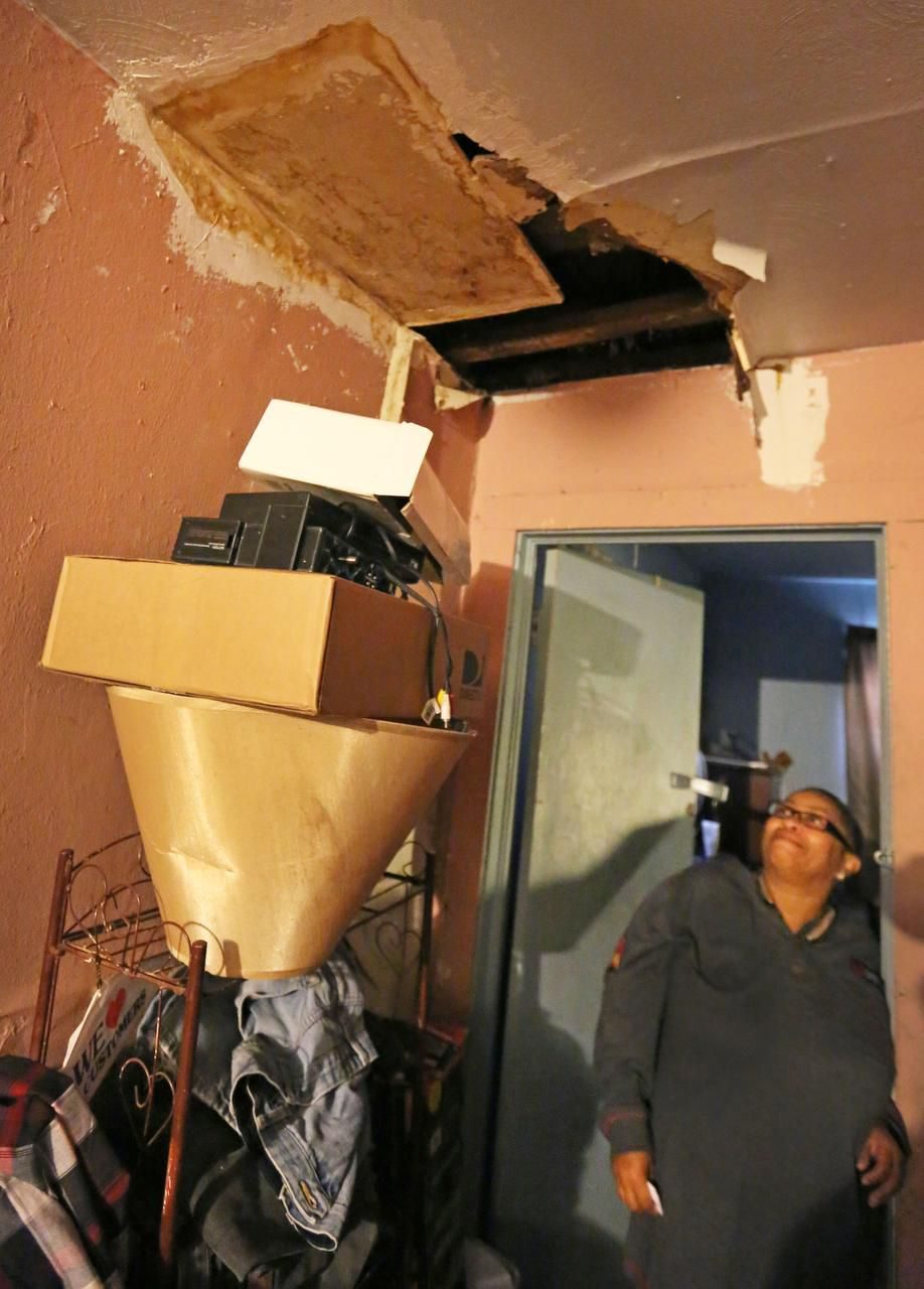 Joanne Bonner looks  through a hole in the ceiling in the Topletz-owned home her family rents for $400 a month on Lawrence Street in South Dallas.