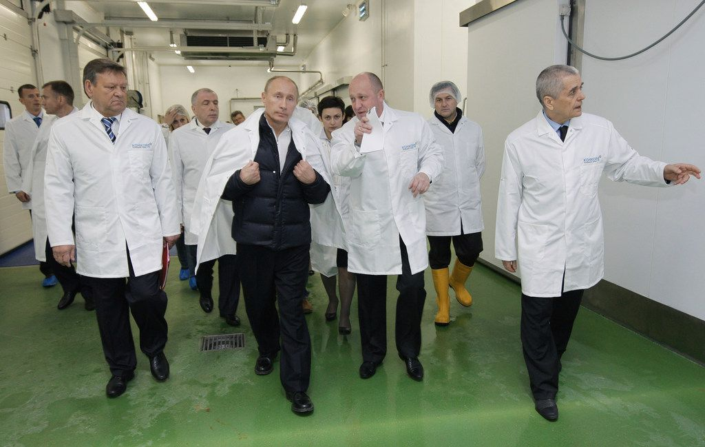Yevgeny Prigozhin (center right) with President Vladimir Putin at his school lunches factory outside St. Petersburg, Russia, on Sept. 20, 2010. The 2018 United States indictment is among the clearest documents yet in stating outright that Prigozhin, a businessman grown fabulously wealthy off government contracts, controls the Internet Research Agency, despite denials from him and the Kremlin.