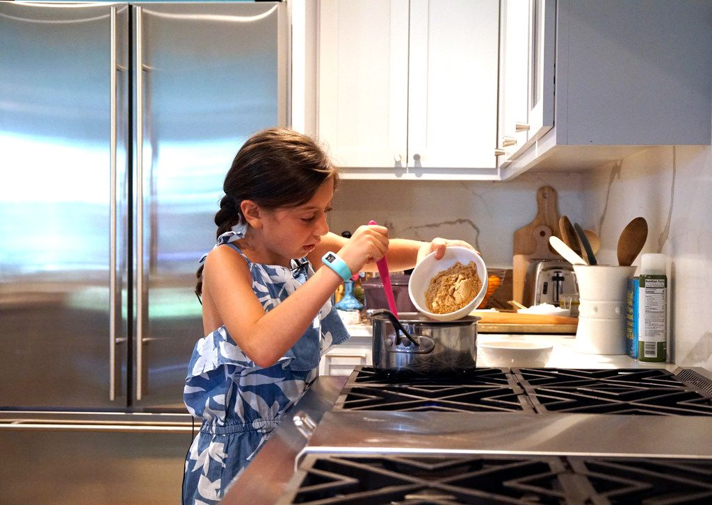 Sophie Massad (8) adds ingredients for granola bars at her home in Dallas.