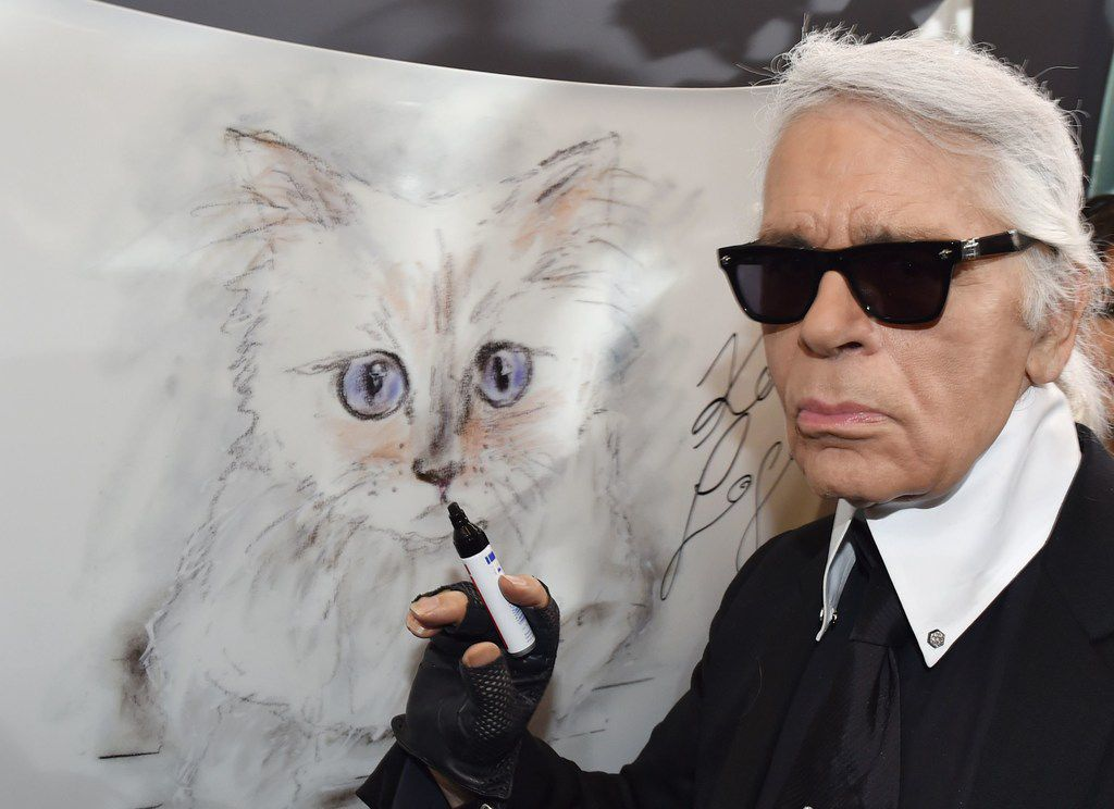 """In this file photo taken on Feb. 3, 2015, German fashion designer, artist and photographer Karl Lagerfeld poses next to a painting of his cat """"Choupette"""" during the inauguration of the show """"Corsa Karl and Choupette"""" at the Palazzo Italia in Berlin. Lagerfeld has died at the age of 85."""