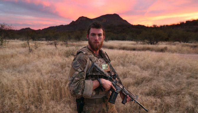 """CONDADO DE PIMA, ARIZONA. James, de 24 años, es un voluntario paramilitar civil que trabaja con Arizona Border Recon (AZBR), un grupo compuesto por unos 200 ex militares estadounidenses en su mayoría, quienes ayudan a controlar la actividad fronteriza. """"Ellos no se consideran una milicia, de hecho no les gusta la palabra vigilante. Permanecen una semana varias veces al año en zonas rurales   donde no están los agentes. Traen su propio armamento y carpas, pero no tienen ninguna autoridad policial, así que no pueden capturar a la gente, sino que intentan intimidarla para que desistan de cruzar. James me dijo que era estudiante universitario y que lo hacía por  razones patrióticas"""". Foto: John Moore / Getty Images"""