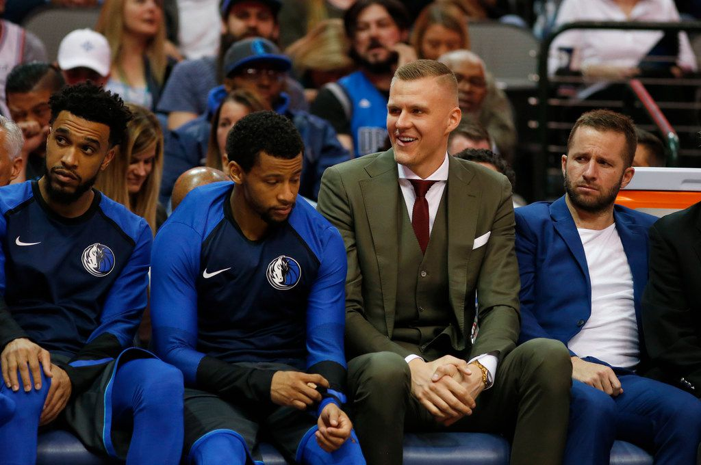 Dallas Mavericks forward Kristaps Porzingis (6) laughs from the bench during the first half of play against the Philadelphia 76ers at the American Airlines Center in Dallas on Monday, April 1, 2019. Dallas Mavericks guard Courtney Lee (1) (left), Dallas Mavericks guard Trey Burke (23) (second from left), Dallas Mavericks guard J.J. Barea (5) (right) sit next to Porzingis. (Vernon Bryant/The Dallas Morning News)