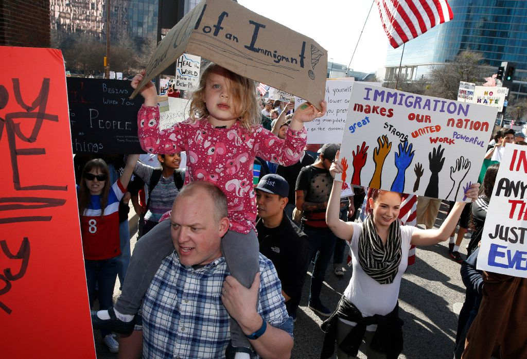 Tjepke Heeringa holds his daughter Lulu Heeringa, 4, during a protest for immigrant and refugee communities in downtown Dallas on February 18, 2017.