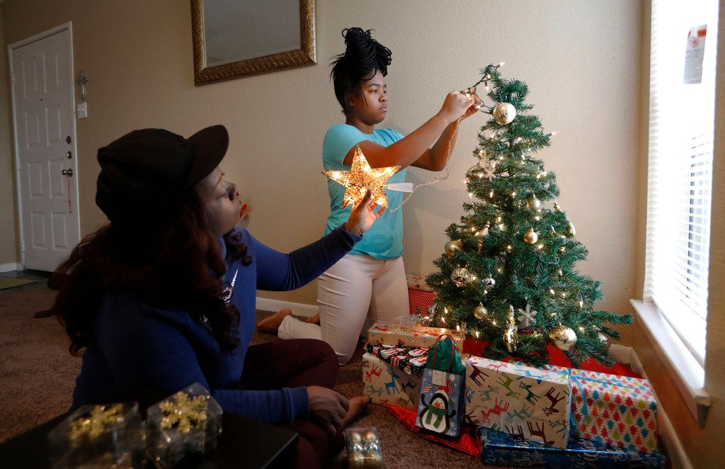 Ebony Green, left, and her daughter Amaris Dobbins decorates their Christmas tree in their new apartment in northeast Dallas on Friday, December 22, 2017. (David Woo/The Dallas Morning News)