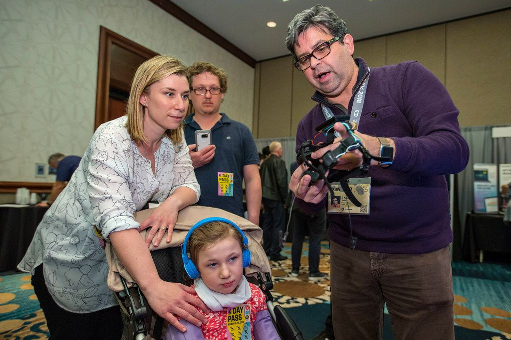 Thierry Hubert (right), CEO of Darwin Ecosystem, speaks with Amber Weigl and her husband Dan Weigl at South by Southwest in March. The Weigl family got day passes specifically to talk to Darwin Ecosystem and learn how it might be able to benefit their daughter Catherine Weigl, 7, who has Rett's Syndrome.
