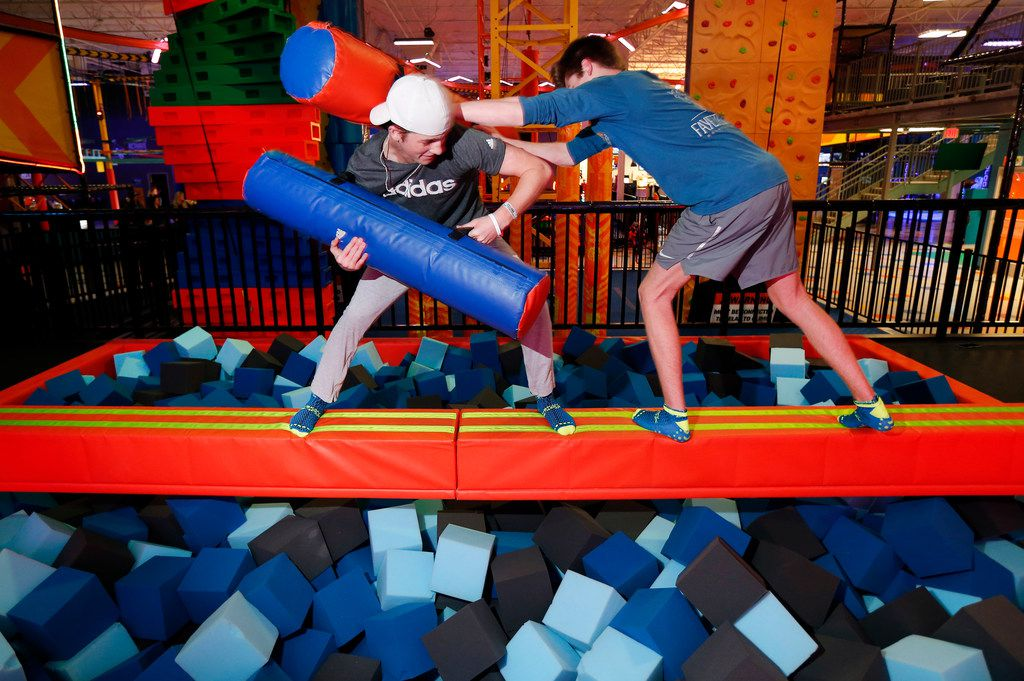 Friends Kaleb Bright (left) and Drew McCastlain of Keller compete on the Battle Beam at Urban Air Adventure Park's flagship location in Southlake.