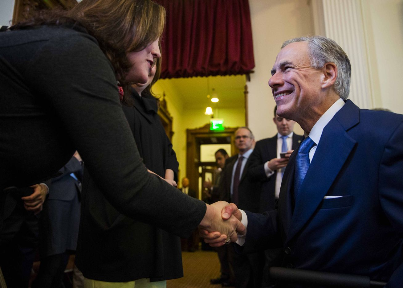Gov. Greg Abbott shakes hands with a supporter on the floor of the House during the first day of the 85th Texas Legislative Session  at the Texas State Capitol in Austin.