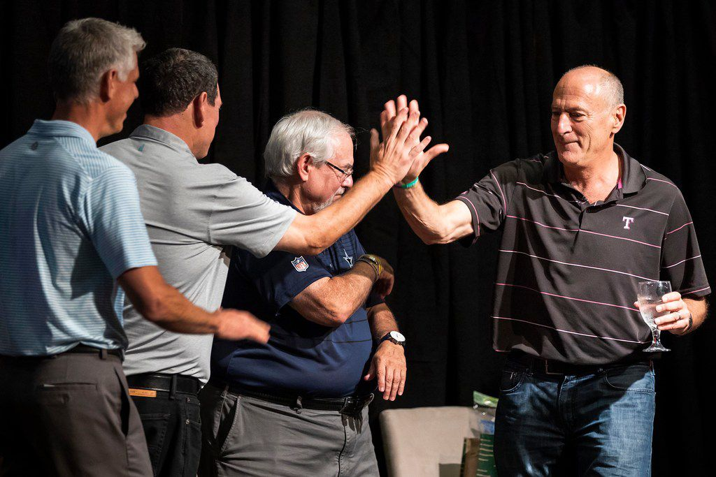 Texas Rangers play-by-play broadcaster Eric Nadel (right) high fives Dallas Mavericks play-by-play broadcaster Chuck Cooperstein as he takes the stage with Dallas Cowboy play-by-play broadcaster Brad Sham (second from right) and Craig Miller of The Ticket (left) during Talk of the Town, an annual charity event, on Thursday, July 12, 2018, in Dallas. (Smiley N. Pool/The Dallas Morning News)
