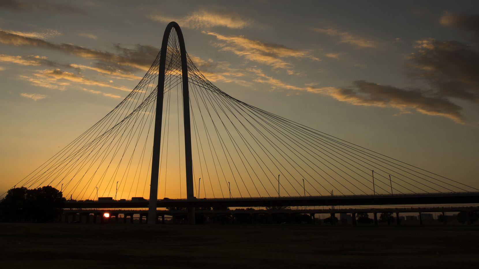 The sun sets behind the Margaret Hunt Hill Bridge on July 3.
