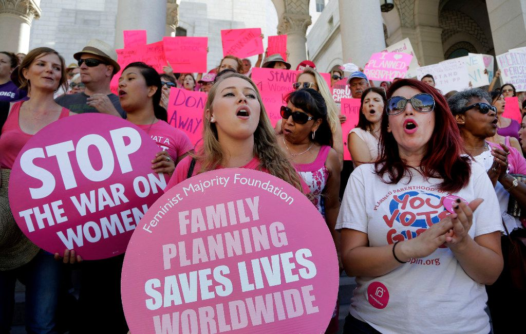 "In this Sept. 9, 2015, file photo, Planned Parenthood supporters rally for women's access to reproductive health care on ""National Pink Out Day'' at Los Angeles City Hall. One of President-elect Donald Trump's first, and defining, acts next year could come on Republican legislation to cut off taxpayer money from Planned Parenthood. (Associated Press)"