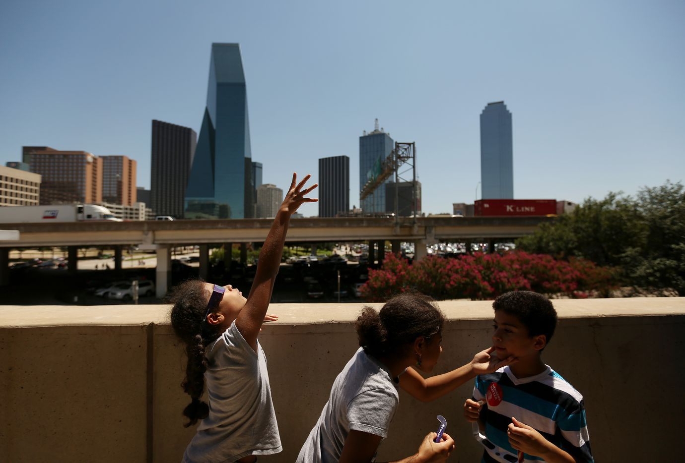 Iliana Harris, 10, of Dallas, reaches for the sky during a solar eclipse outdoor watch party at the Perot Museum of Nature and Science.