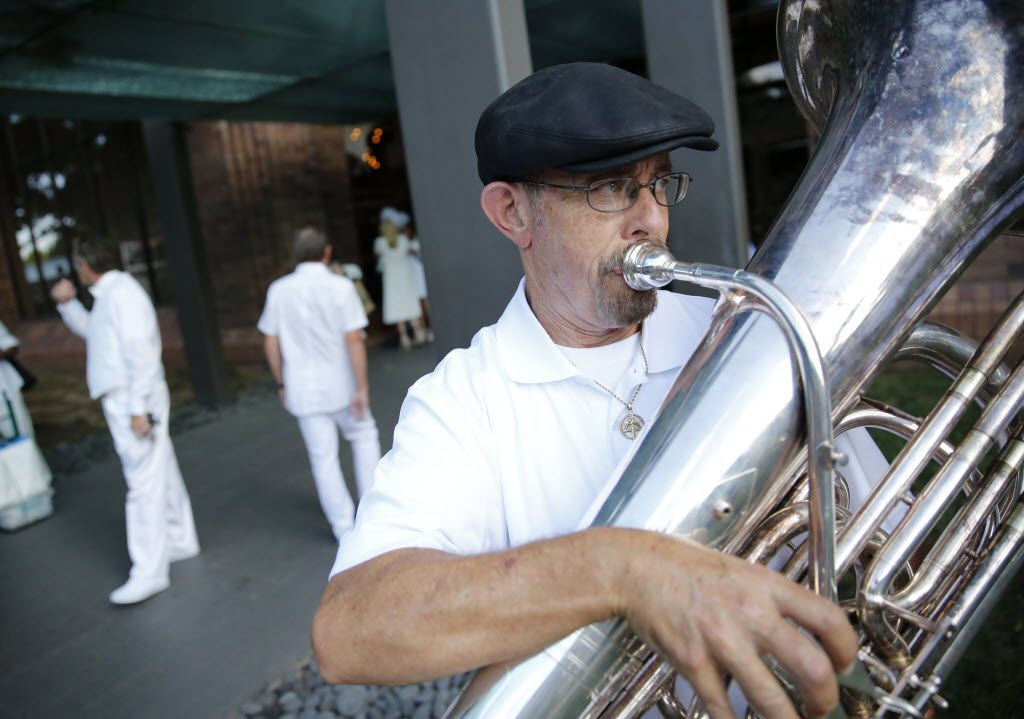 Eugene LeBeaux, a member of the Razzmajazz band, plays the tuba outside the Hilton Anatole, a rendezvous point for guests attending the inaugural Diner en Blanc Dallas in Dallas on Sept. 17, 2015. Exactly 1,678 people attended the event, which requires dinner guests to dress all in white and bring their own tables, chairs and centerpieces. As per tradition, the location was kept private leading up to the event.